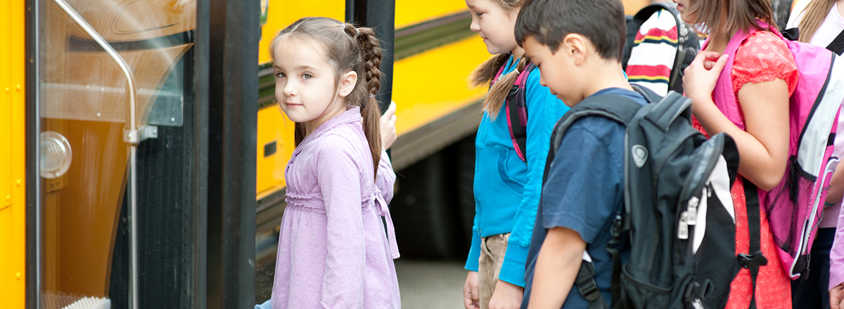 smiling girl getting on bus