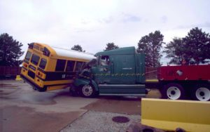 Photo of semi-truck slamming into a school bus during a side impact crash test demonstration.